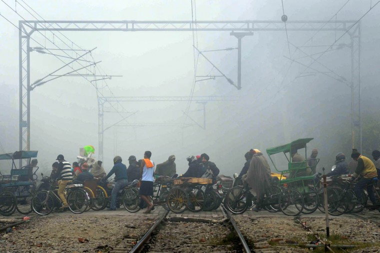Indian commuters make their way in dense fog, over a railroad crossing in Amritsar. Heavy fog has disrupted road, rail and air traffic across northern India. (Narinder Nanu/Getty Images)