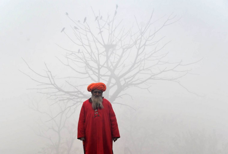 A Pakistani Sufi stands on a foggy street in Lahore. The ongoing spell of dense fog and freezing weather conditions has continued to disturb the scheduled arrival and departure of flights and trains in Pakistan's Punjab province. (Arif Ali/Getty Images)