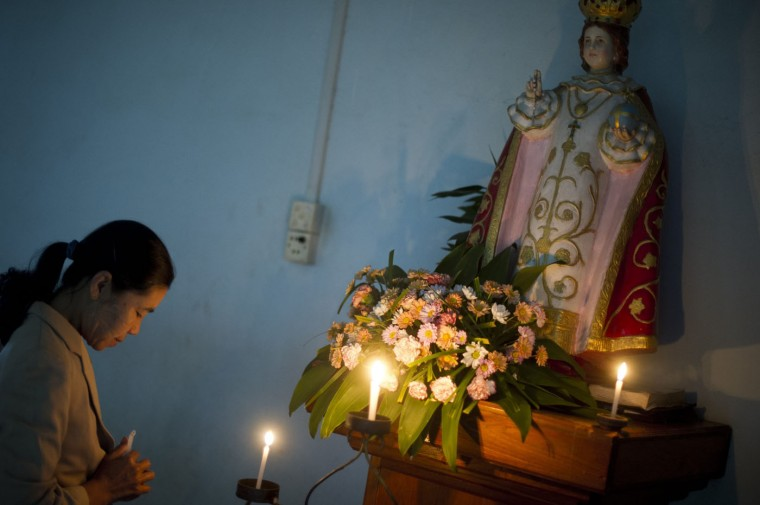 This photo taken on October 12, 2014 shows a woman praying at a church in Loikaw, Kayah state, eastern Myanmar. Six decades after its first saint was murdered for his faith amid a bloody civil war, Myanmar's Catholic Church is stepping up calls for peace and religious tolerance as it celebrates its 500th anniversary. AFP/Getty/Ye Aung Thu