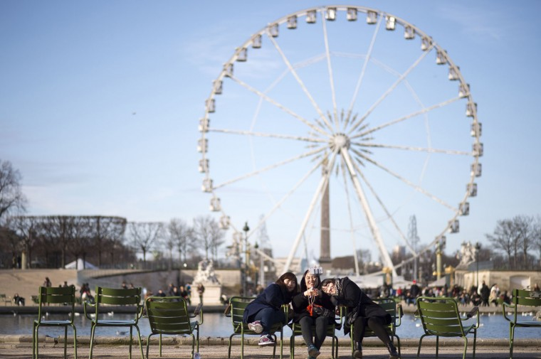 A picture taken on December 25, 2014 shows tourists taking a selfie in the Tuilerie Garden in Paris with a ferris wheel in the backround. AFP/Getty/Lionel Bonaventure