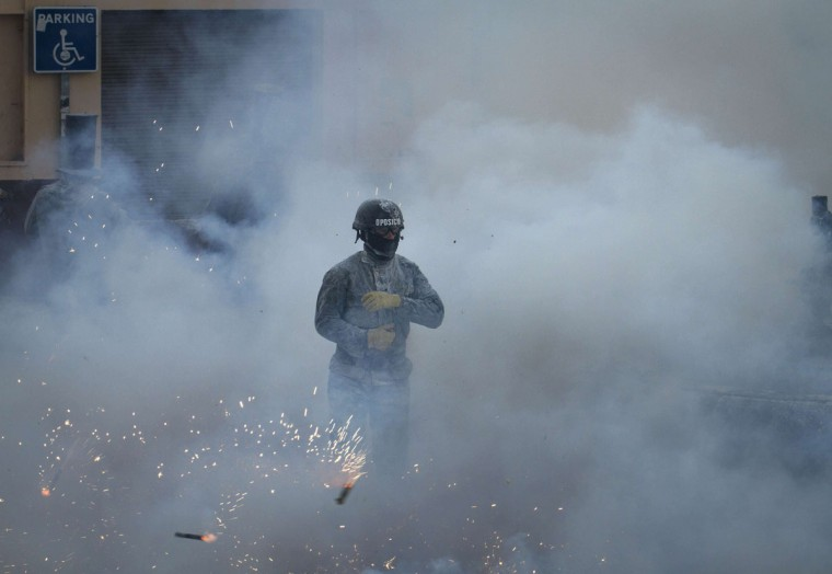 "A reveler, dressed in a mock military uniform, takes part in the battle of ""Enfarinats"", a flour fight, in the town of Ibi, south-eastern Spain, on December 28, 2014. (JAIME REINA/AFP/Getty Images)"