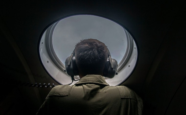 A member of the Indonesian military looks out of the window during a search and rescue (SAR) operation for missing Malaysian air carrier AirAsia flight QZ8501, over the waters of the Java Sea on December 29, 2014. Multinational teams searched on December 29 for any sign of the AirAsia plane missing off Indonesia with 162 people on board, but one top official warned it was likely at the bottom of the sea. (Juni Kristwanto/AFP/Getty Images)
