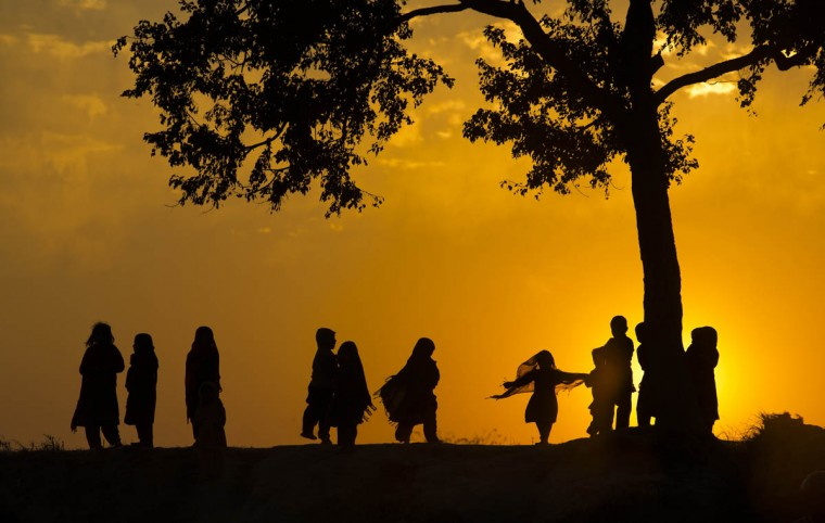 Children displaced from Pakistani tribal areas due to fighting between security forces and militants play under a tree during the last sunset of the year on the outskirts of Islamabad, Pakistan, Wednesday, Dec. 31, 2014. (B.K. Bangash/AP photo)