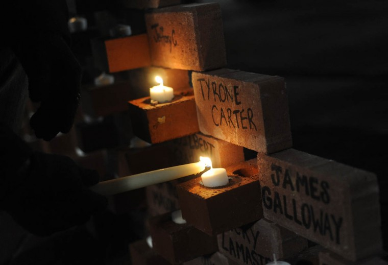 Candles are lit in brick wall inscribed by names of those who died this year from homelessness. (Algerina Perna/Baltimore Sun)