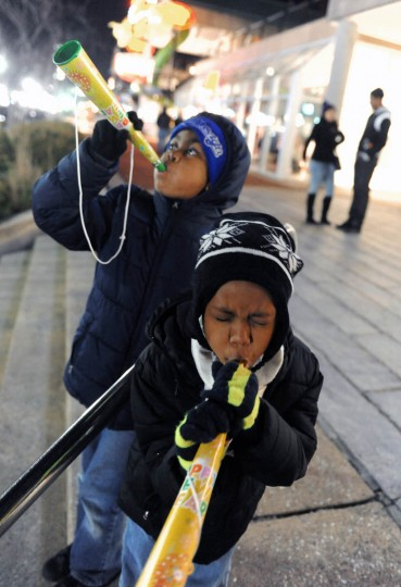 Nathaniel Howard, 7, foreground, and brother Regrick, of Sumter, South Carolina, warm up their toy horns for the New Year celebration at the Inner Harbor. Baltimore's New Year's Eve Spectacular welcomes the new year with music and a fireworks and light show display at midnight over the Inner Harbor. (Kenneth K. Lam/Baltimore Sun)