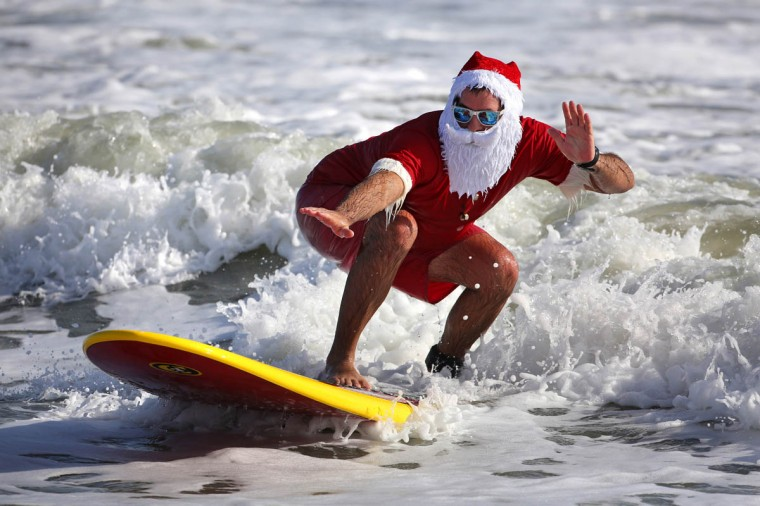 Surfers don Santa outfits during the Surfing Santas of Cocoa Beach fundraiser in Cocoa Beach, Fla. Hundreds dressed in costume and braved the chilly surf for the event, now in its sixth year. Proceeds support the Cocoa Beach Surf Museum and Grind for Life, a local charity that assists cancer patients. (Joe Burbank/Orlando Sentinel)