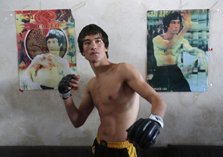 Abbas Alizada, who calls himself the Afghan Bruce Lee, poses for a picture in front of Bruce Lee posters after exercising in Kabul December 9, 2014. (Mohammad Ismail/Reuters)