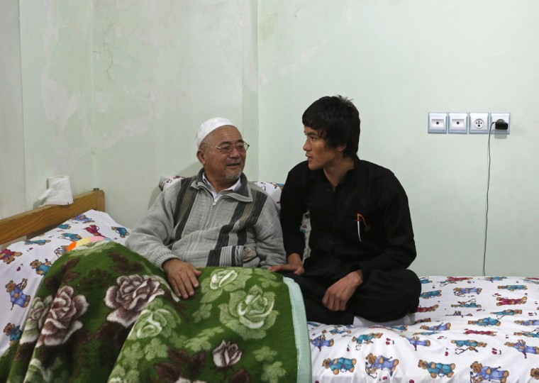 Abbas Alizada, who calls himself the Afghan Bruce Lee (R), talks to his father at their house in Kabul December 9, 2014. (Mohammad Ismail/Reuters)
