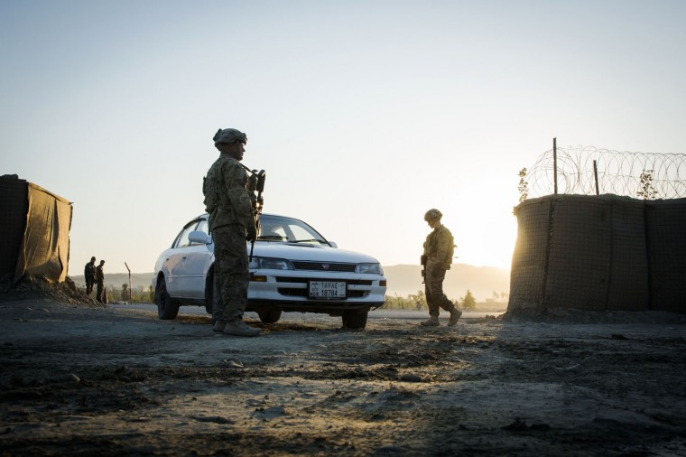 U.S. soldiers from 3rd Cavalry Regiment flag car to stop to be screened for explosives near forward operating base Gamberi in the Laghman province of Afghanistan December 14, 2014.