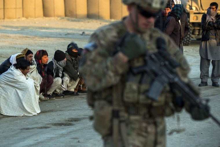 A U.S. soldier from the 3rd Cavalry Regiment stands near local men who wait to be biometrically screened near forward operating base Gamberi in the Laghman province of Afghanistan December 14, 2014.