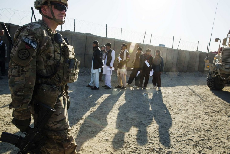 A U.S. soldier from the 3rd Cavalry Regiment stands near local men waiting to be biometrically screened near forward operating base Gamberi in the Laghman province of Afghanistan December 14, 2014.