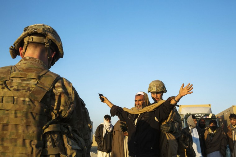 U.S. soldiers from the 3rd Cavalry Regiment interact with men selected to be biologically screened near forward operating base Gamberi in the Laghman province of Afghanistan December 14, 2014.