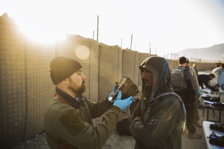 Contractors use a machine to capture biological data of local Afghan men near forward operating base Gamberi in the Laghman province of Afghanistan December 14, 2014.