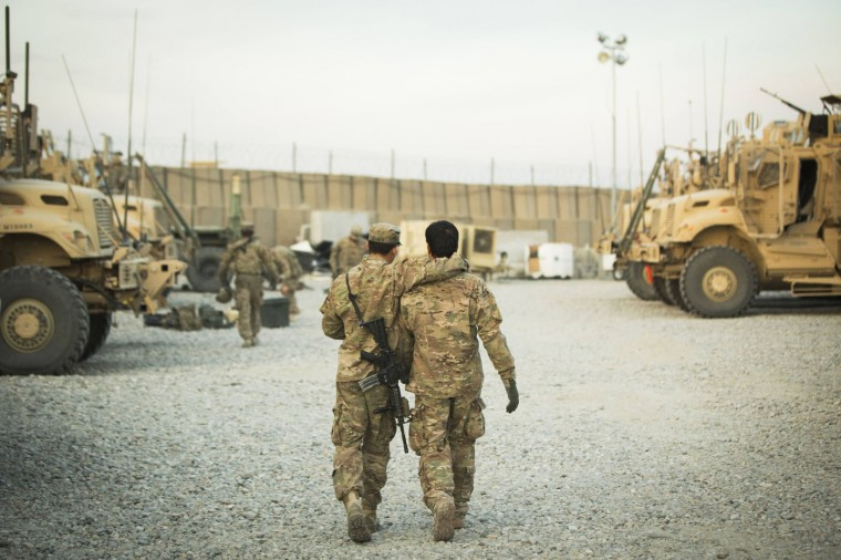A U.S. soldier from the 3rd Cavalry Regiment walks with the unit's Afghan interpreter before a mission near forward operating base Gamberi in the Laghman province of Afghanistan December 11, 2014.