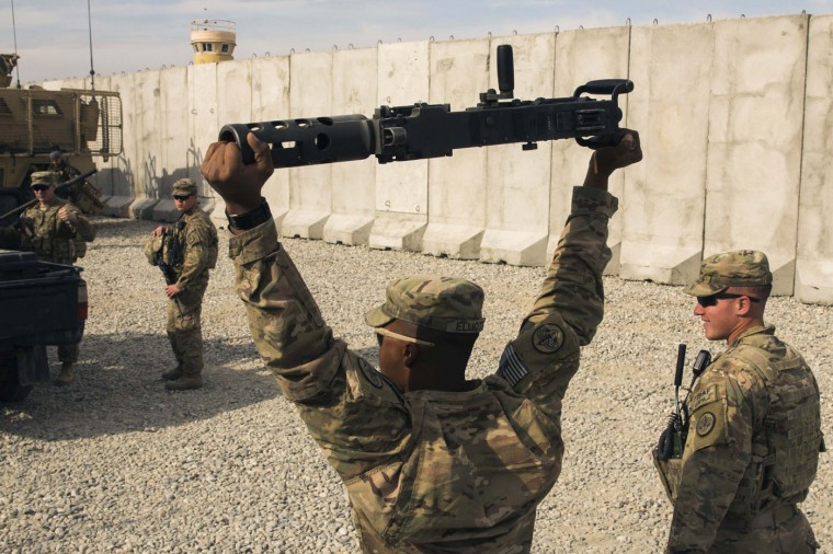 A U.S. soldier from the 3rd Cavalry Regiment carries a machine gun part after a mission at forward operating base Gamberi in the Laghman province of Afghanistan December 12, 2014.