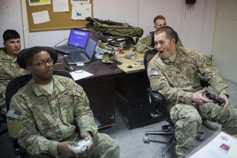 U.S. soldiers from the 3rd Cavalry Regiment play video games after returning from a mission at forward operating base Gamberi in the Laghman province of Afghanistan December 12, 2014.