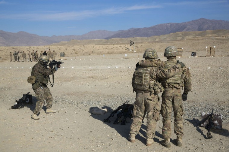 U.S. soldiers from the 3rd Cavalry Regiment watch a member of the Polish military on a shooting range as part of a joint training mission, near forward operating base Gamberi in the Laghman province of Afghanistan December 12, 2014.