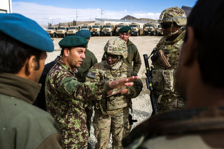 U.S. soldiers from the 3rd Cavalry Regiment speak with Afghan National Army soldiers about their logistics while on an advising mission at the Afghan National Army headquarters for the 203rd Corps in the Paktia province of Afghanistan December 21, 2014.