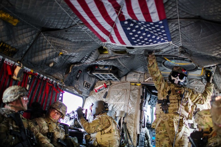 A crew member of a CH-47 Chinook helicopter stands above U.S. soldiers from the 3rd Cavalry Regiment as they fly to an advising mission at an Afghan National Army headquarters for the 203rd Corps in the Paktia province of Afghanistan December 21, 2014.