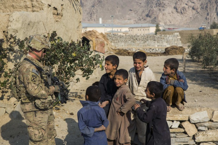 A U.S. soldier from the 3rd Cavalry Regiment talks to Afghan children during an advising mission to an Afghan police station constructed by ISAF near Jalalabad in the Nangarhar province of Afghanistan December 20, 2014.