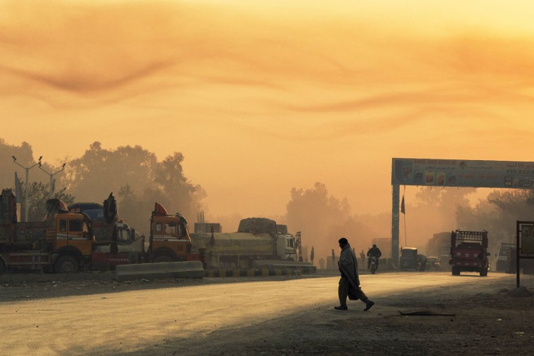 The rising sun lights smoke in the air as a man crosses the street near Forward Operating Base Fenty in the Nangarhar province of Afghanistan December 19, 2014.