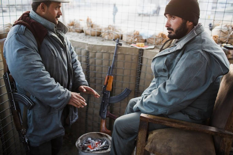 Afghan police warm themselves with hot coals in a pot as they are visited by U.S. soldiers from Grim Company of the 3rd Cavalry Regiment near Forward Operating Base Fenty in the Nangarhar province of Afghanistan December 19, 2014.