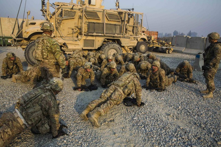 U.S. soldiers from Grim Company of the 3rd Cavalry Regiment drop to push-up position as they return from a mission near Forward Operating Base Fenty in the Nangarhar province of Afghanistan December 19, 2014.