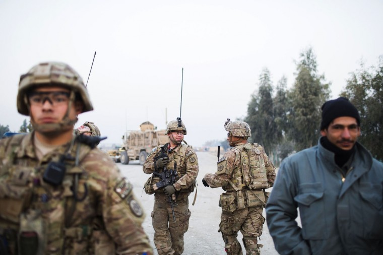 U.S. soldiers from Grim Company of the 3rd Cavalry Regiment walk down the street during a mission near Forward Operating Base Fenty in the Nangarhar province of Afghanistan December 19, 2014.