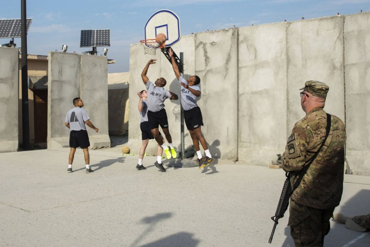 U.S. soldiers play basketball on an outdoor court surrounded by concrete blast walls at Forward Operating Base Fenty in Nangarhar province December 18, 2014.