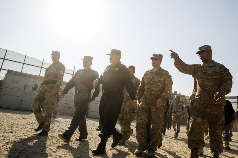 Brigadier General Christopher Bentley (2nd R) walks with Nangarhar provincial chief of police, Major General Fazal Ahmad Shirzad (C), during a visit to an Afghan National police installation in the Nangarhar province of Afghanistan December 16, 2014.