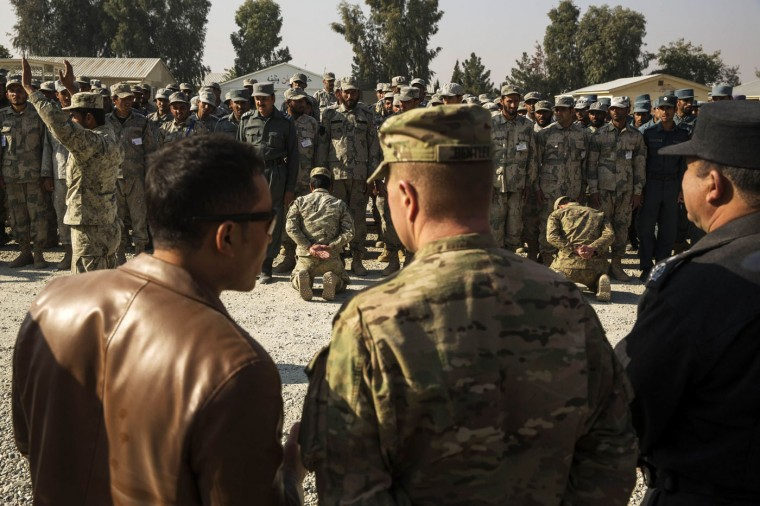 Brigadier General Christopher Bentley (C) watches a demonstration by Afghan police officers with Nangarhar provincial chief of police, Major General Fazal Ahmad Shirzad (R), during a visit to an Afghan National police installation in the Nangarhar province of Afghanistan December 16, 2014.