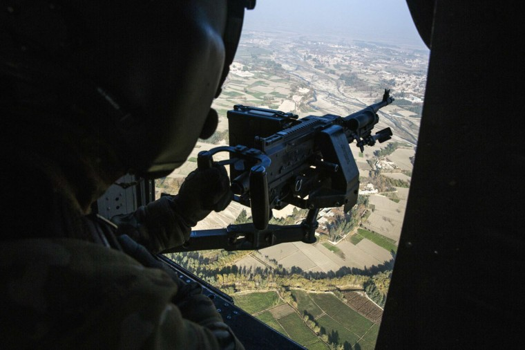 A crew member mans a machine gun on a U.S. Blackhawk helicopter as it flies over the city of Jalalabad after taking Brigadier General Christopher Bentley to inspect an Afghan National police installation in the Nangarhar province of Afghanistan December 16, 2014.