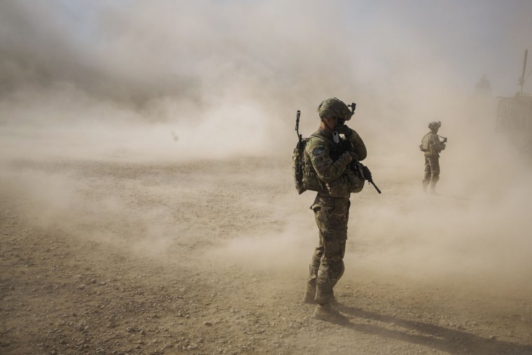 U.S. soldiers cover their faces from the dust blown around by the rotors of a helicopter during a visit to an Afghan National police installation in the Nangarhar province of Afghanistan December 16, 2014.