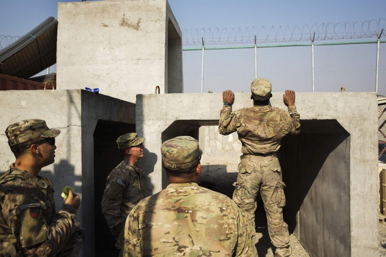 U.S. soldiers from the 3rd Cavalry Regiment engage in a pull-up contest before a training mission at forward operating base Gamberi, in the Laghman province of Afghanistan December 15, 2014.