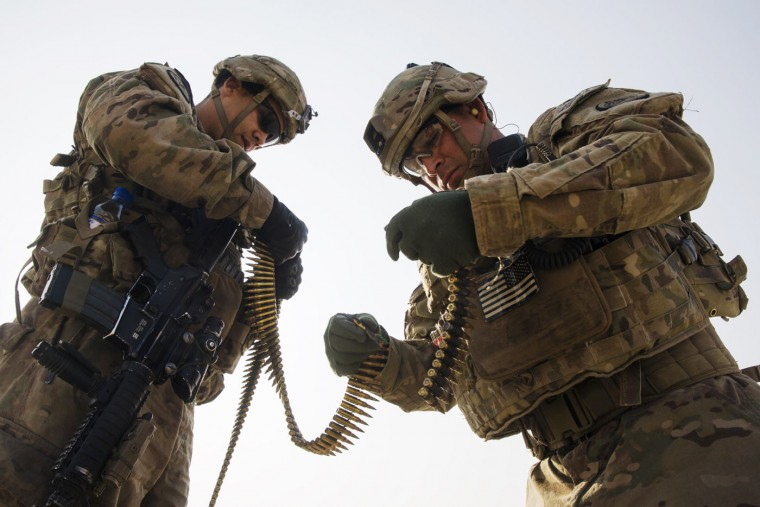 U.S. soldiers from the 3rd Cavalry Regiment examine belts of bullets for corroded rounds during a training mission near forward operating base Gamberi, in the Laghman province of Afghanistan December 15, 2014.