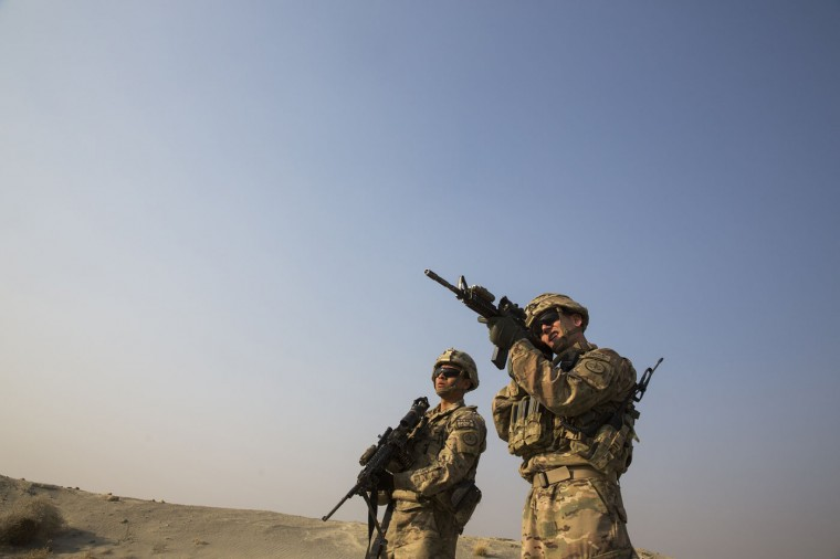 A U.S. soldier from the 3rd Cavalry Regiment uses the optic on his rifle to observe Afghans in the distance, near forward operating base Gamberi, in the Laghman province of Afghanistan, December 15, 2014.