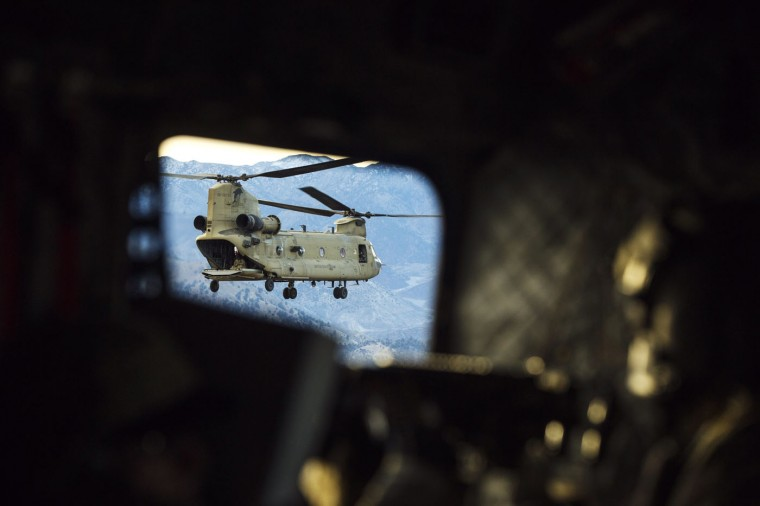 A CH-47 Chinook helicopter from the 82nd Combat Aviation Brigade is seen flying outside of the window of another helicopter carrying U.S. soldiers from the 3rd Cavalry Regiment to an advising mission at an Afghan National Army headquarters for the 203rd Corps in the Paktia province of Afghanistan December 21, 2014.