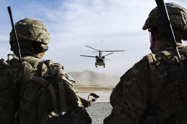 U.S. soldiers from the 3rd Cavalry Regiment watch as CH-47 Chinook helicopter from the 82nd Combat Aviation Brigade lands after an advising mission at the Afghan National Army headquarters for the 203rd Corps in the Paktia province of Afghanistan December 21, 2014.