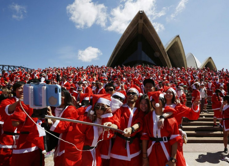 Runners in Father Christmas suits pose for a 'selfie' photo after completing an annual Santa fun run from Darling Harbor to the Sydney Opera House, December 7, 2014. The annual event is held each year as a fundraiser to assist disadvantaged children with equipment and programs to help them live a fuller life. (Jason Reed/Reuters)