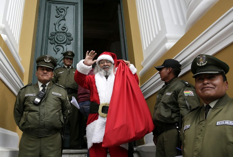 Congressman David Cortez, dressed as Santa Claus, waves at the entrance of the national congress building in La Paz December 18, 2014. Every year Cortez dresses as Santa Claus as he participates in a congress session to wish his colleagues a merry Christmas, reported local media. (David Mercado/Reuters)