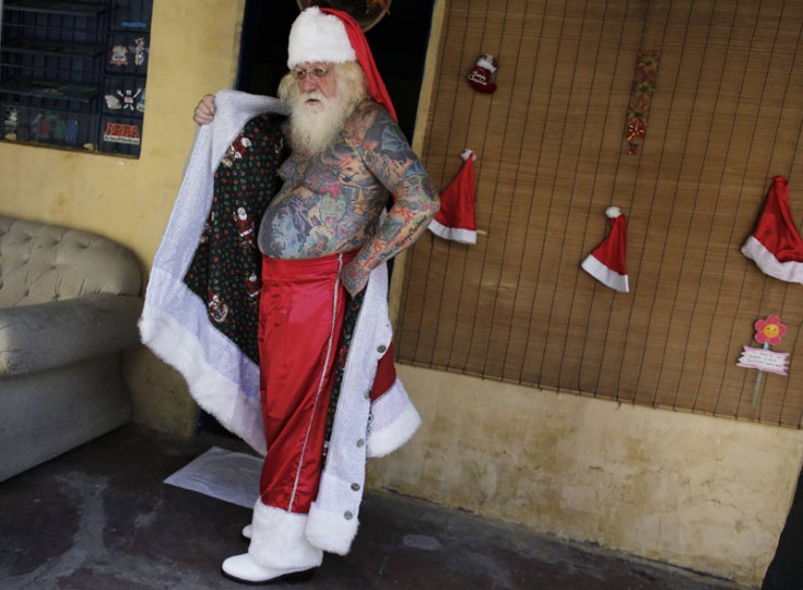 Vitor Martins poses as he puts on his Santa outfit inside his house, before a performance with children in Sao Caetano do Sul's town square, near Sao Paulo, December 7, 2014. Martins has dressed as Santa Claus, working at shopping centers and various events, for fifteen years, and has 94 percent of his body covered in tattoos, with several in reference to Christmas. (Nacho Doce/Reuters)