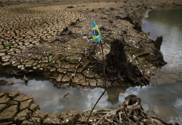 A Brazilian flag is seen on the cracked ground of Atibainha dam, part of the Cantareira reservoir, during a drought in Nazare Paulista, Sao Paulo state December 2, 2014. Brazil's worst drought in 80 years has left the Cantareira system, that provides greater Sao Paulo with most of its water, with the lowest water level on record, with daily rationing becoming common in the region's smaller cities, according to the state authorities and the two main reservoirs serving metropolitan Sao Paulo, South America's largest city, could dry out by February if relief does not arrive in the upcoming rainy season. Pictures taken December 2, 2014. REUTERS/Nacho Doce