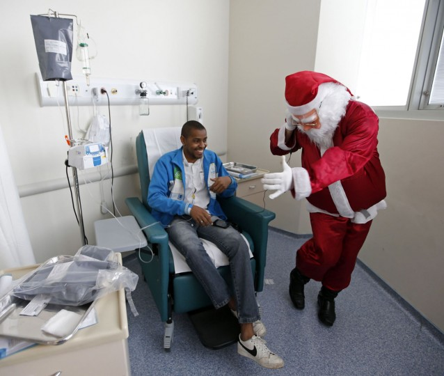 A man dressed as Santa Claus dances while listening to music on headphones borrowed from a cancer patient (L) undergoing chemotherapy in the Cancer Institute in Sao Paulo December 19, 2014. (Paulo Whitaker/Reuters)