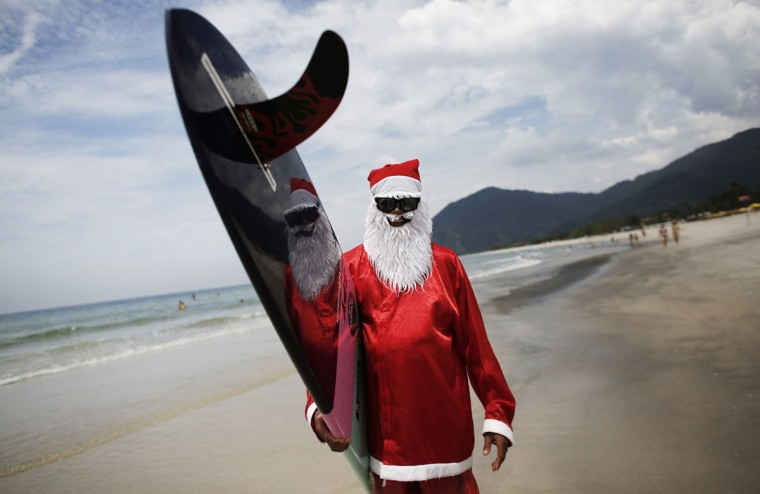 Carlos Bahia, dressed as Santa Claus, poses with his board at the Maresias beach, in the state of Sao Paulo December 9, 2014. In the Southern Hemisphere summer starts on December 1, so while countries in the north are experiencing a white Christmas with grey skies, those in the south are busy surfing and sunbathing in temperatures just shy of 100 degrees Fahrenheit (38 degrees Celsius). Picture taken December 9, 2014. (Nacho Doce/Reuters)