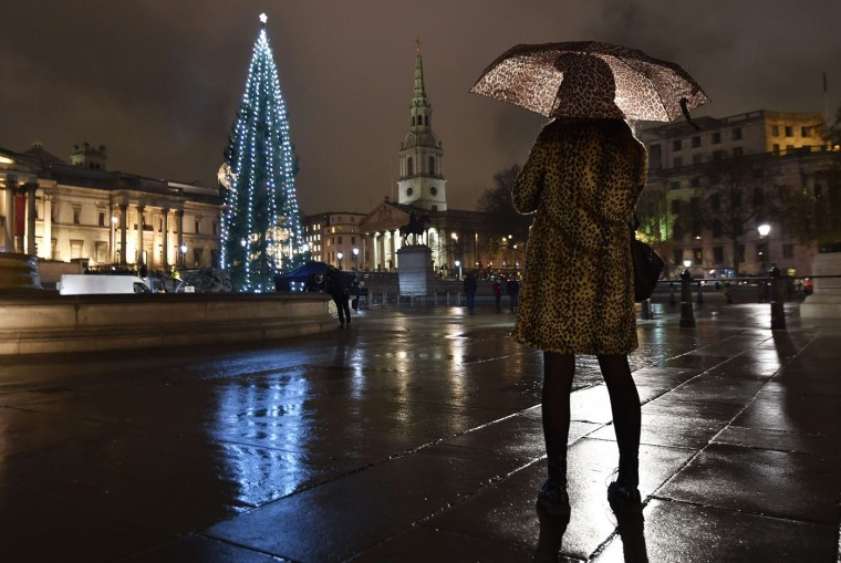 A woman photographs a Norwegian spruce Christmas tree from Oslo after it was lit at Trafalgar Square in central London, December 4, 2014. REUTERS/Toby Melville
