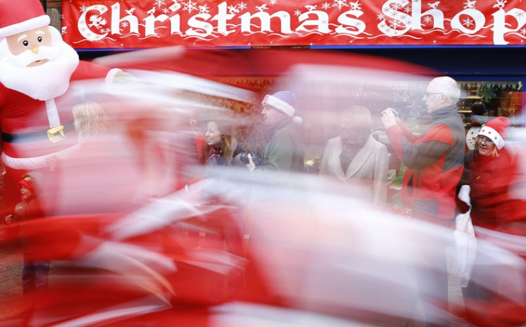 Competitors dressed as Santa Claus sprint past spectators during an annual charity Santa fun run in Loughborough, central England December 7, 2014. (Darren Staples/Reuters)
