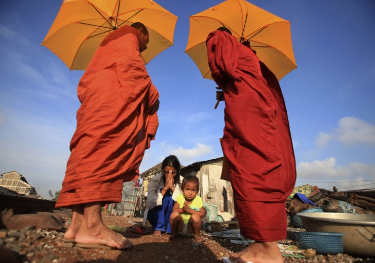 A woman and her daughter pray after offering alms to Buddhist monks near a railway track in Phnom Penh December 2, 2014. (REUTERS/Samrang Pring)