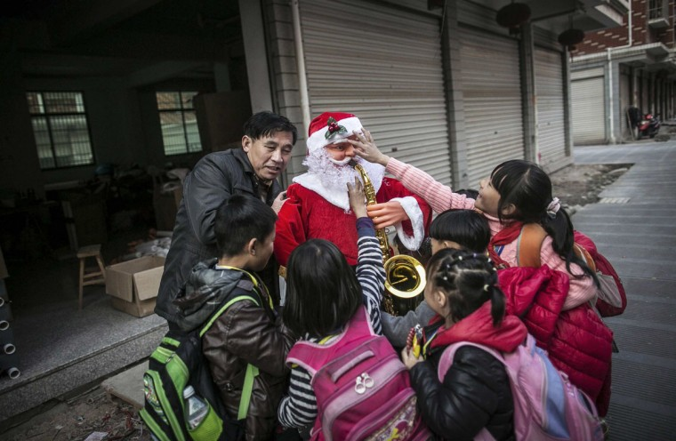 A worker holding a newly made Santa Claus model is surrounded by students in Yiwu, Zhejiang province December 4, 2014. (China Daily/Reuters)