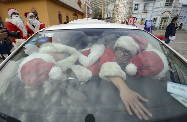 Staff dressed as Santa Claus try to squeeze into a car at a theme park in Changsha, December 18, 2014. Nineteen staff managed to get inside the car during the game. Picture taken December 18, 2014. (China Daily/Reuters)