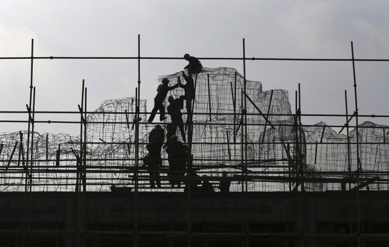 Laborers work on the scaffoldings at a construction site in Kunming, Yunnan province, December 22, 2014. China issued rules requiring real-estate owners to register their holdings with authorities, a major step in the fight against official corruption that should make it harder for property speculators to evade regulations. Picture taken December 22, 2014. (REUTERS/Stringer)